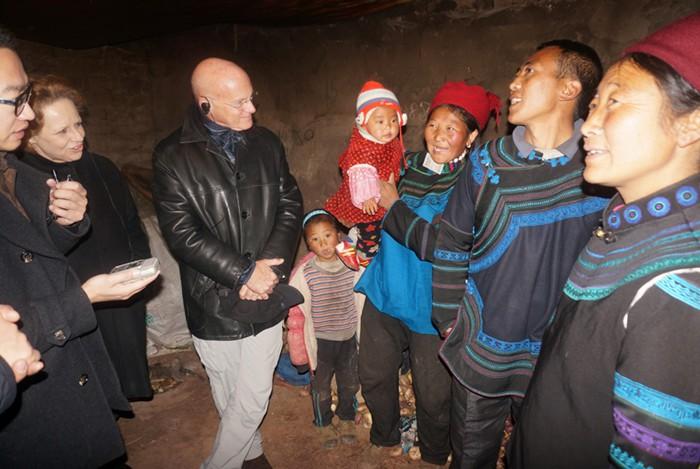 """2015年1月15日,在四川省凉山彝族自治州昭觉县跳坝村的一户村民家里,联合国儿童基金会驻东亚及太平洋地区主任丹尼尔•图尔(Daniel Toole)和联合国儿童基金会驻华代表麦吉莲(Gillian Mellsop)与这家人围坐在火堆旁。25岁的尔古乌合一家得到了联合国儿童基金会在当地提供的项目支持。这对夫妻告诉丹尼尔他们三岁的儿子和一岁的女儿都是在医院分娩的,他们给儿子起名为医生,意为""""在医院出生。"""" ©UNICEF/China/2015/杨静婕"""